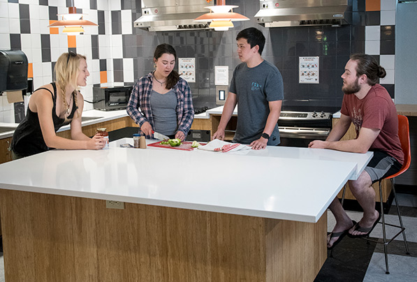four students cooking in Finley Hall kitchen