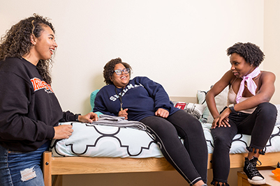 three students talking in residence hall room