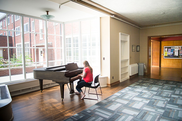 Student playing piano in a Sackett hall lounge