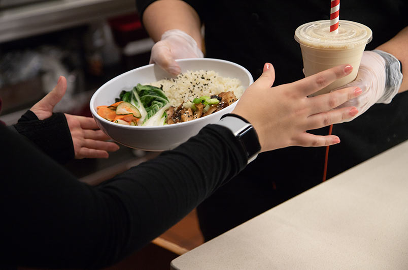 worker handing rice bowl to customer
