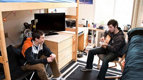 two college students in a double-sized room talking
