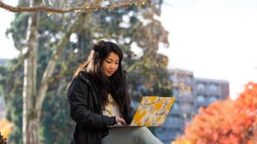 student using laptop on bench outside