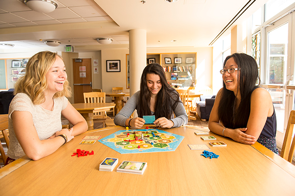 Students playing a board game in West Hall lounge